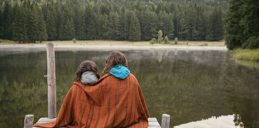 Mother and daughter sitting on a jetty with lake and forest in front